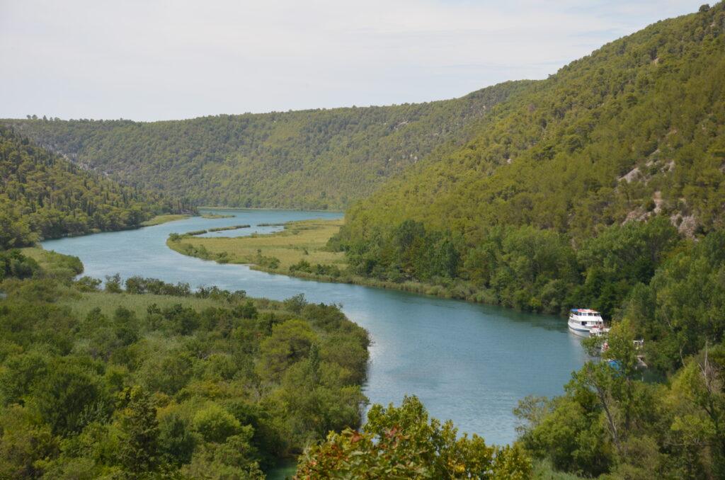 The river Krka. On the right high, green mountains. On the right a boat docked in the river. On the left and in the middle grass lands.