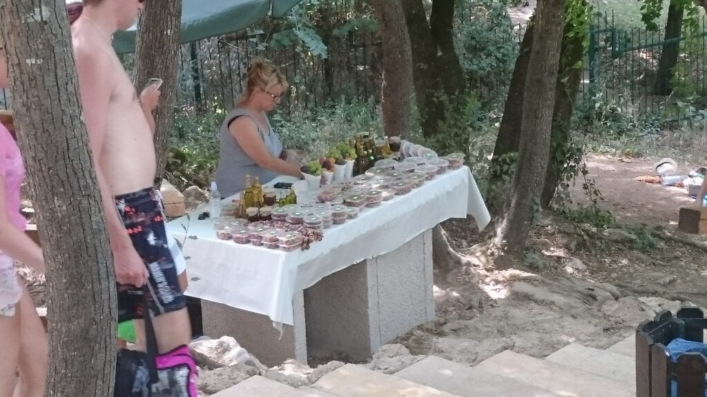 Stall with goodies. Next to stairs, people in swimming gear walking down on the left. A woman behind the stall. The stall is a concrete table with a white cloth on it and cups with fruit, some small bottles and lots of cups with a lid.