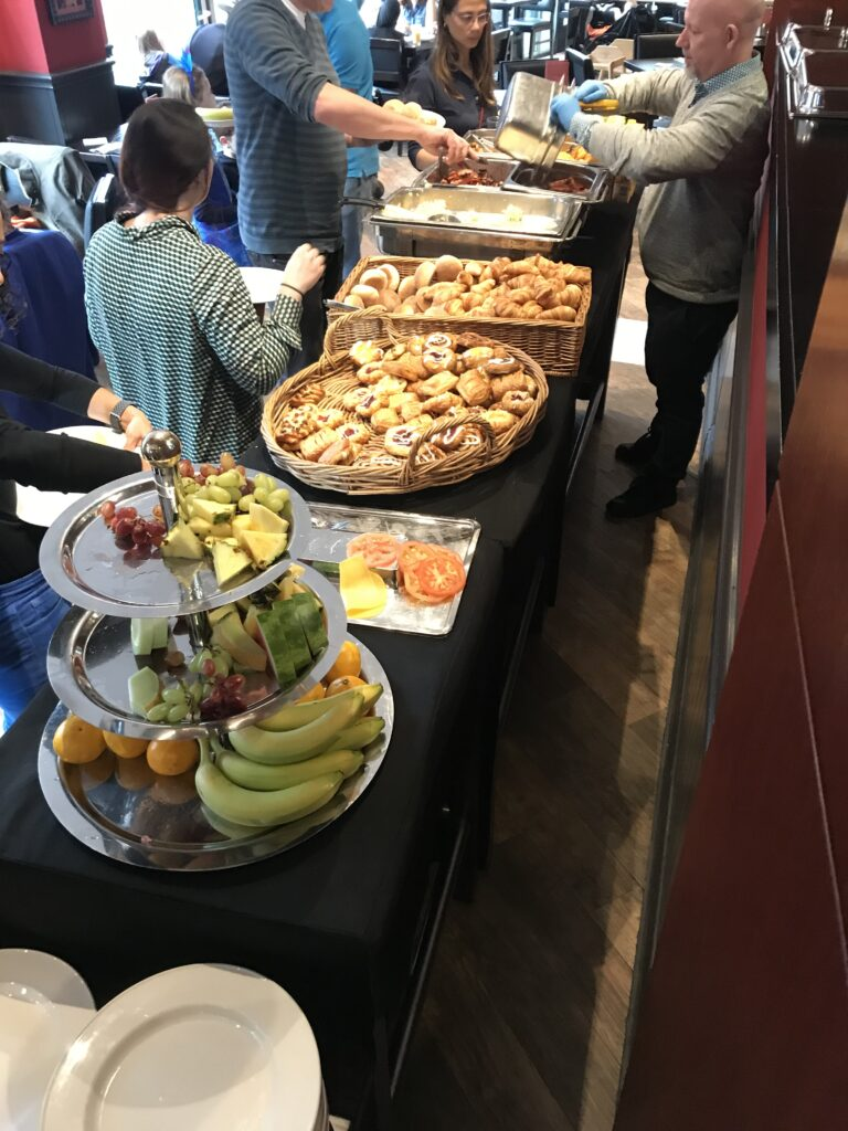 The breakfast buffet at the Hard Rock cafe, fruit and pastries. People in line getting stuff. A waiter filling one of the bowls.