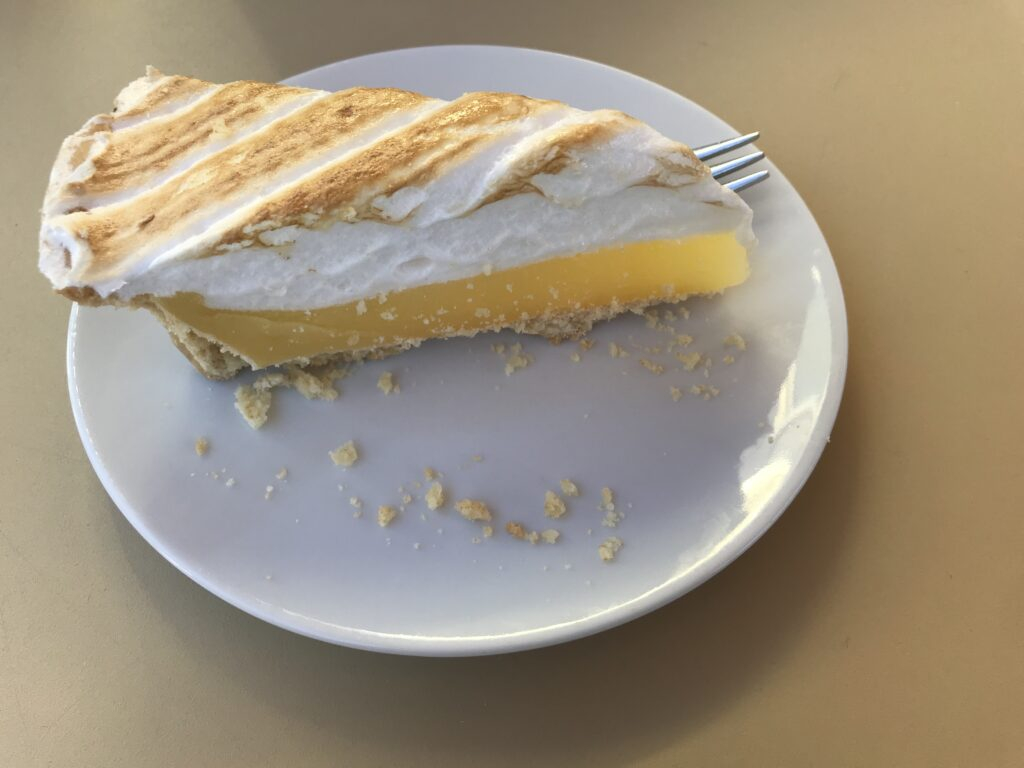 Lemon cake on a plate with a fork behind the cake.