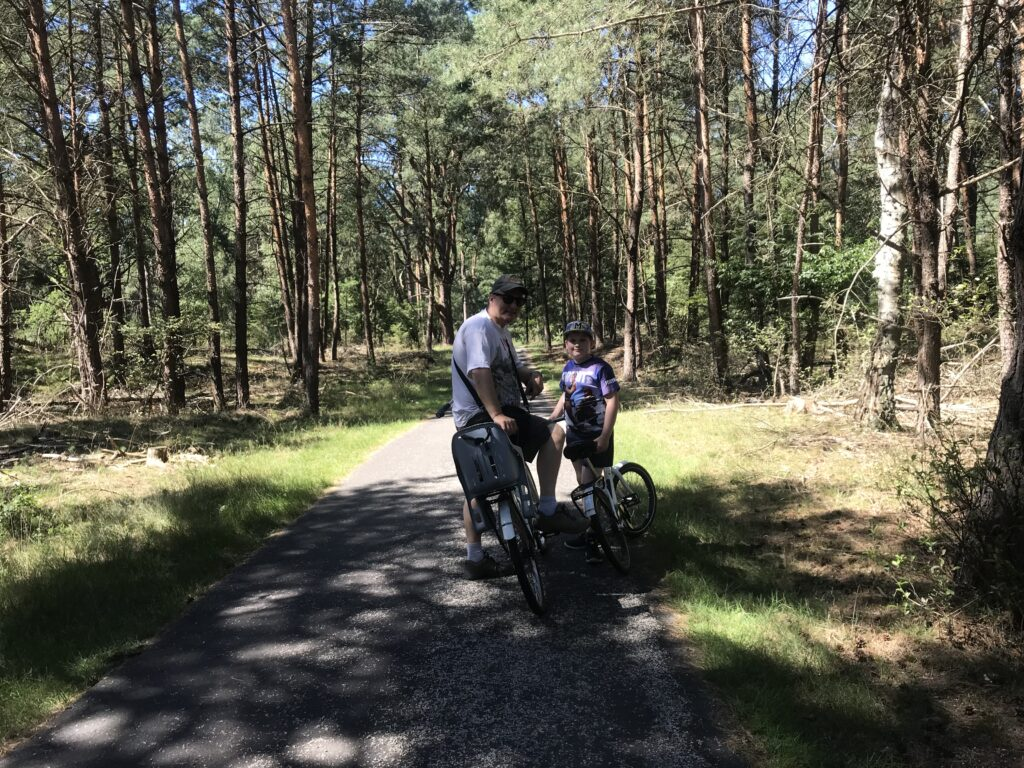 Paul and Yuri with white bikes in the forest on a biking path
