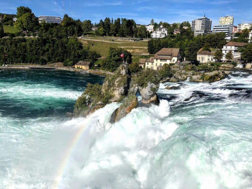 Rhine Falls with a rainbow over the drop down. Grass fields, trees and houses in the back