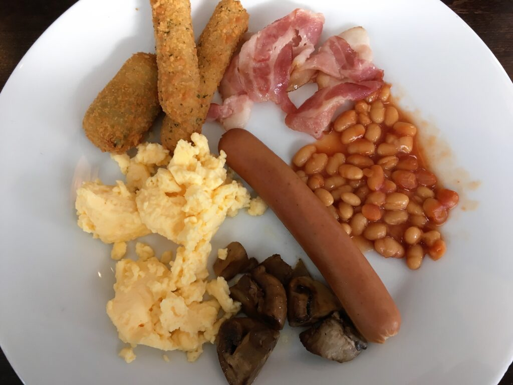 Some of the options available at the breakfast. White beans with tomato sauce, a sausage, baked mushrooms, scrambled eggs, bacon, and some fried stuff