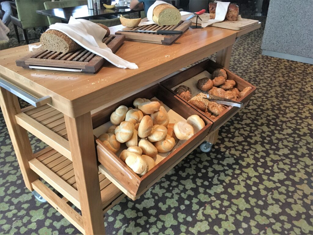 The bread station with buns in drawers under neat the desk, Bread to slice off on top.