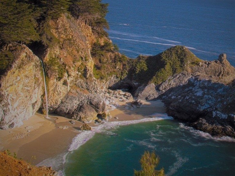 McWay Falls, down below, dropping down on the beach and then flowing into the ocean. Coming off a cliff.
