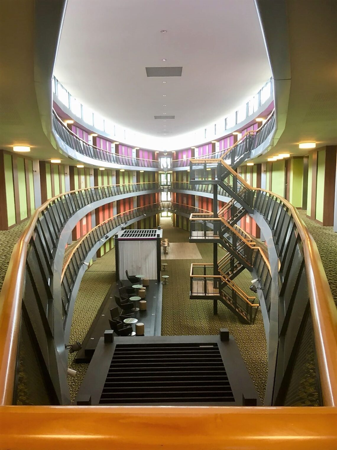 The Atrium, 4 floors, with different colored doors. In the middle open space, down chairs with coffee tables and closed off cubes.