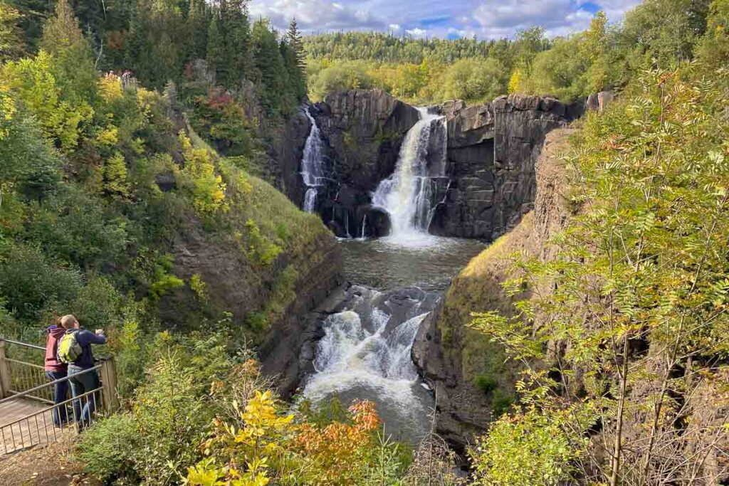 Grand Portage, in the far back dropping down a rock into the river, which cascades again further on. Surrounded by greens on the rocks/mountains