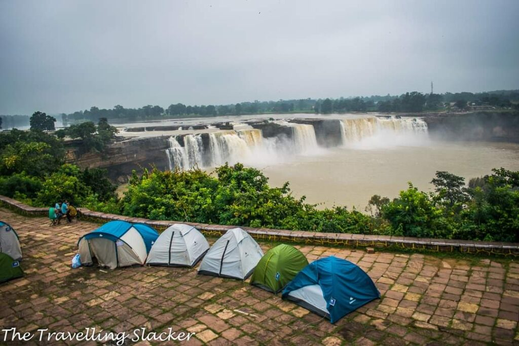 Chitrakote Fall, behind the falls, flowing iver a wide range of a cliff, with some rocks in between. In fromnt 5 tents on tiles