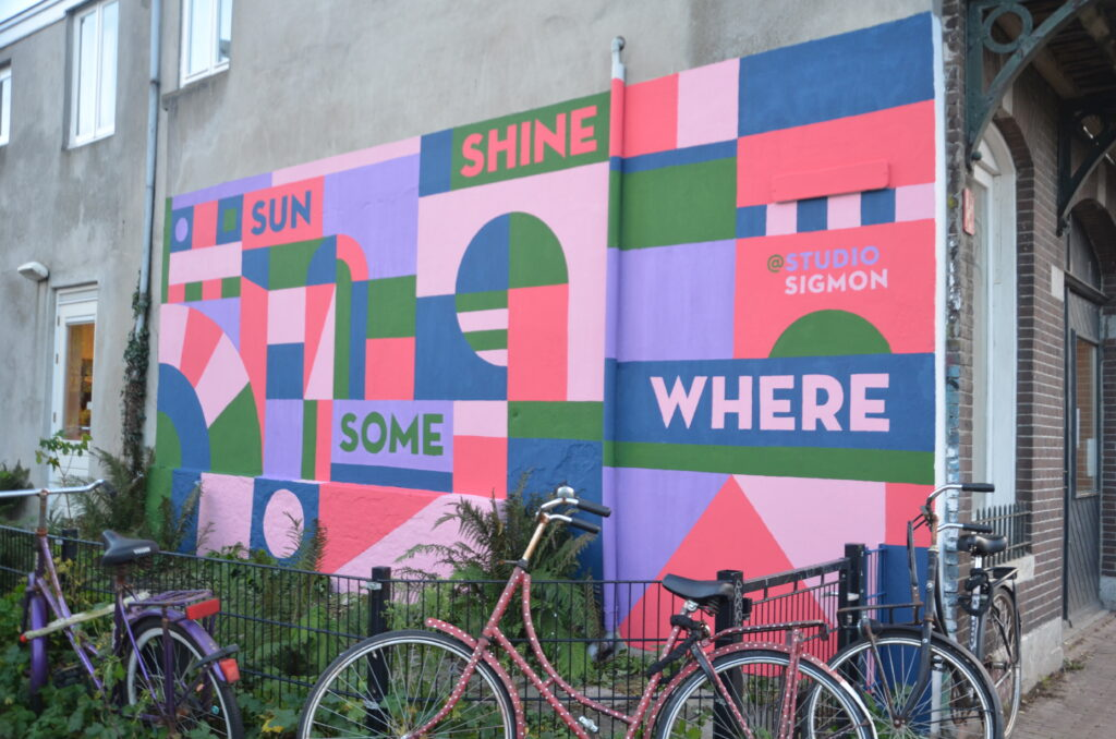 Sun Shine Some Where, a mural with these words and pink, blue, green  and purple colors