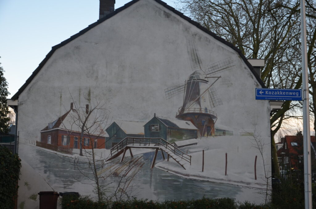 Snowy mural with a mill, a small creek with logs drifting on it, and a farm