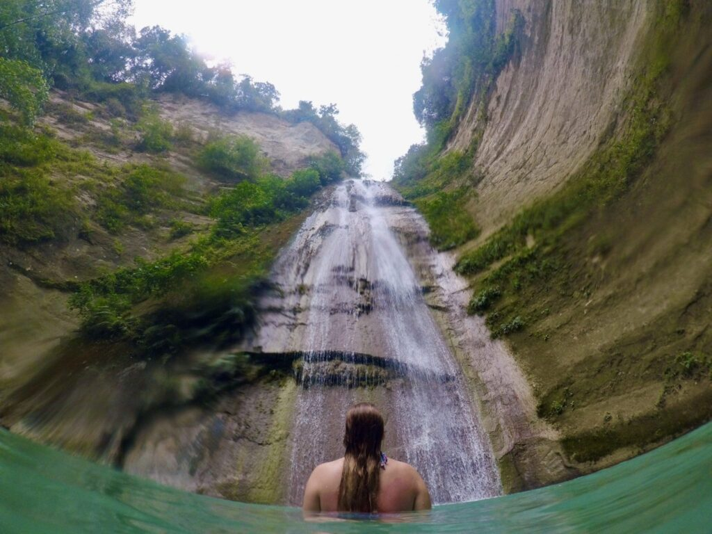 Dau Falls streaming down a high rock/mountain into a pool. Seen from below on the edge of the pool (natural) with a woman in the water, seen from behind