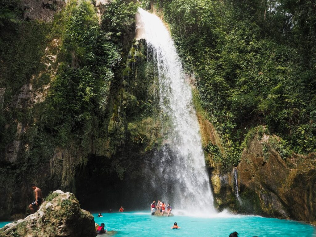 Inambakan Falls A fall drops down in a pool where people are swimming, with lush green surrounding it on the rocks