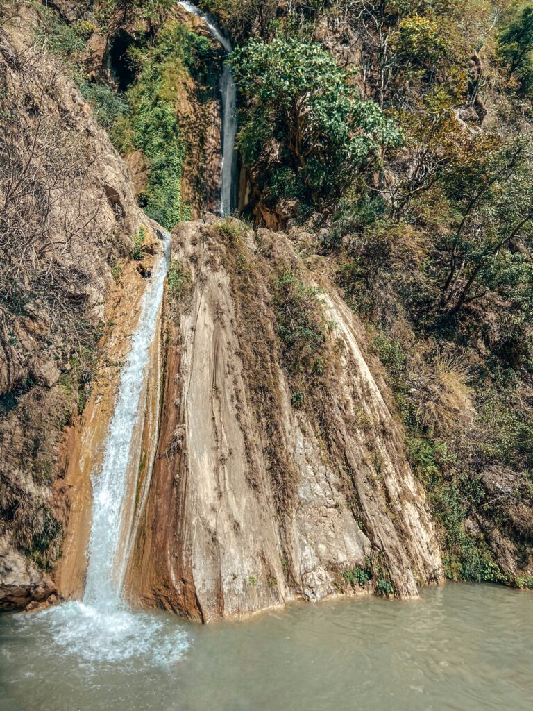 Neer Garh Waterfall , a really small stream flows down on the left side of a rock into a pool