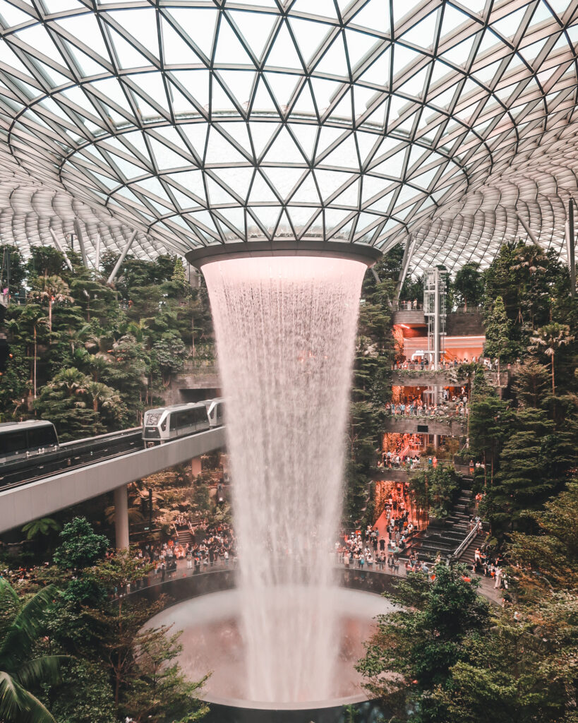 Rain Vortex, a fall drops down from a decorated glass ceiling, inside a large room, with trees and a monorail on the left