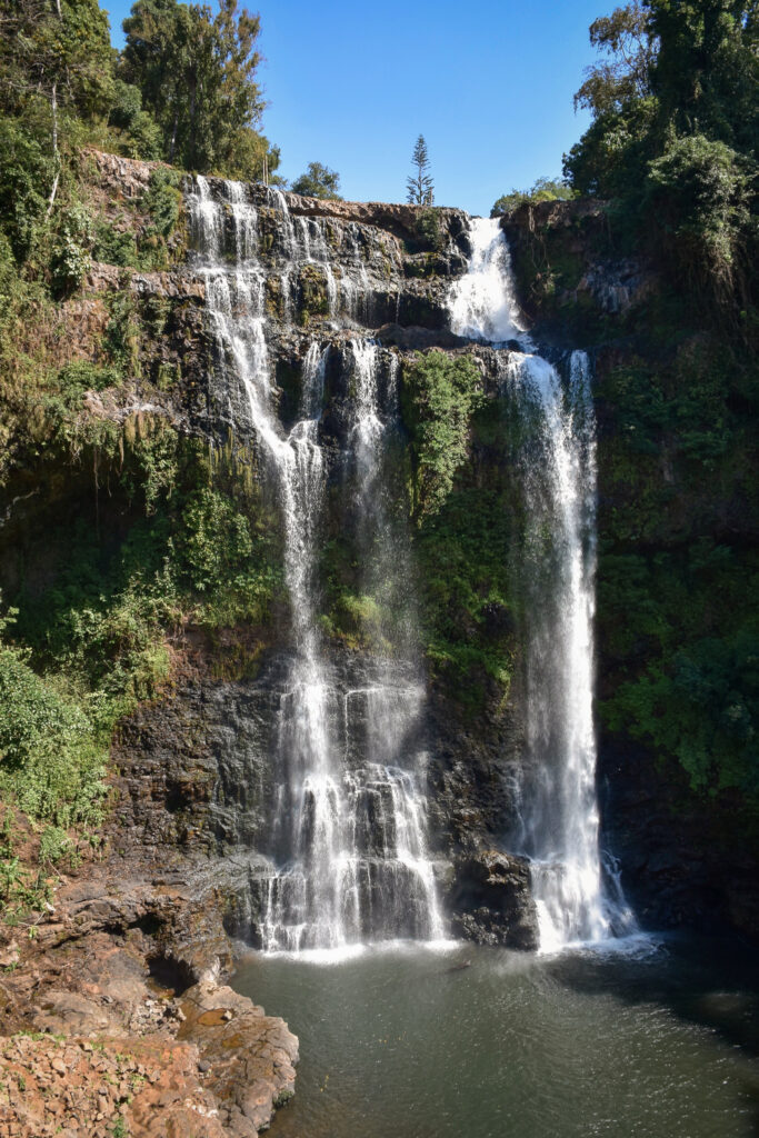 Tad Yuang Waterfall a fall flowing and dropping donwn over rocks/cliff with several traps, green moss on a large part of the rock