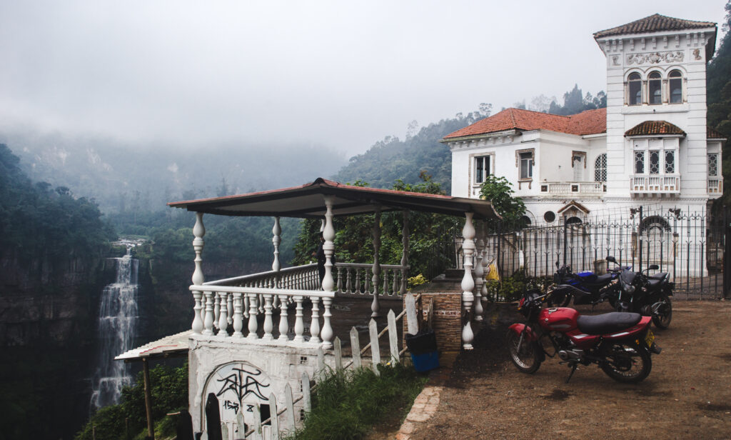 Tequendama Falls on the right side, below is flowing down. With fog above. To the left a building/house with gazebo with a view on the falls. Motorbikes parked next to the gazebo.