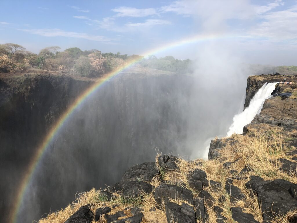 Victoria Falls, from the back and side, you only see a small part of the falls. A rainbow over it.