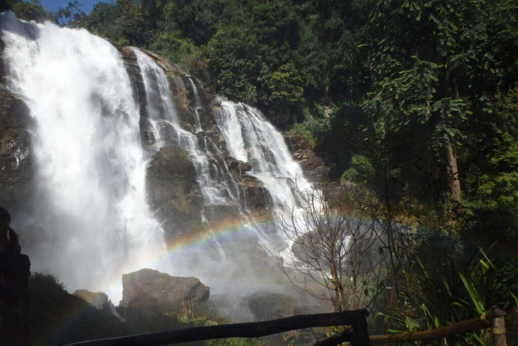 Wachirathan Waterfall a rainbow in front of the falls, dropping down on rocks from a wide cliff