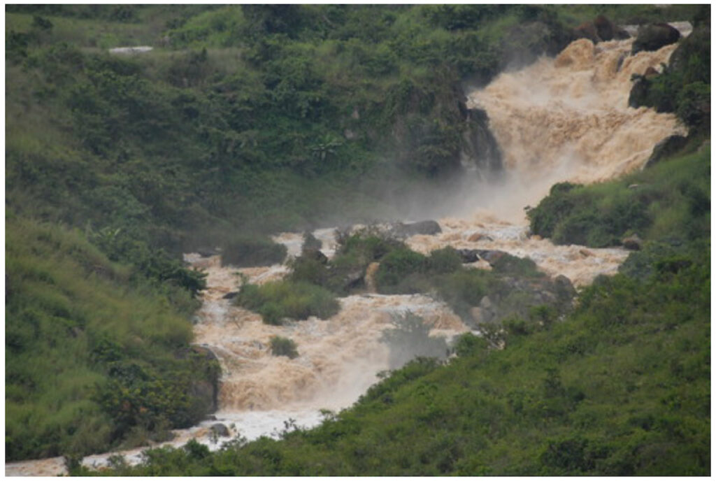 Webuye Falls with green trees/island in on the flatter tracks of the river. It thunders down several times in the river