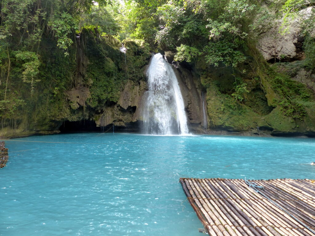 Kawasan Falls a pool where a fall drops down into at the back in the middle. In front on the right a raft. A cliff from rocks and with trees on it