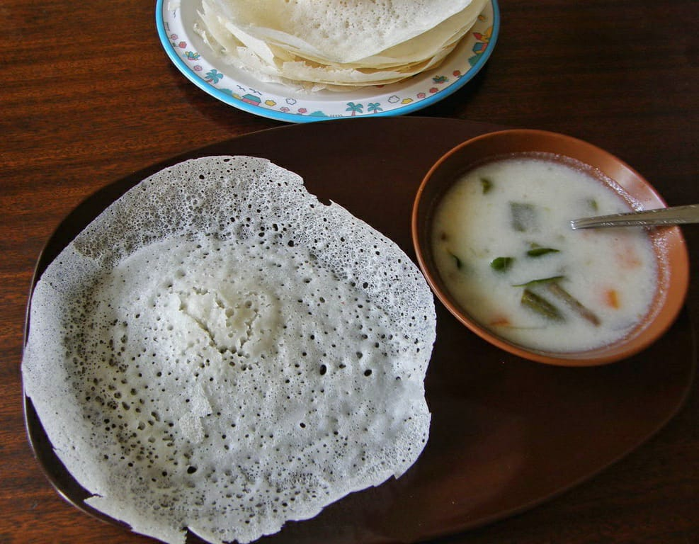 Appam and stew, stew in a bowl, appam on a plate and one lose appam on a plate in front