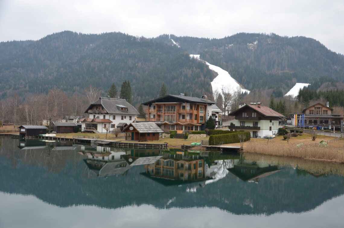 Weissensee in Austria, with a perfect reflection of the houses and mountains in the lake. Some snow on the mountain.
