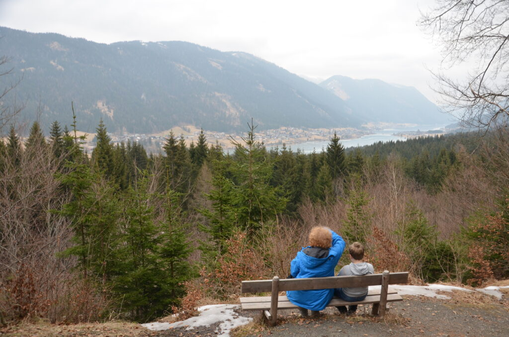 Yuri and I watching the Weissensee during a hike, on a wooden bench, forest between us and the lake