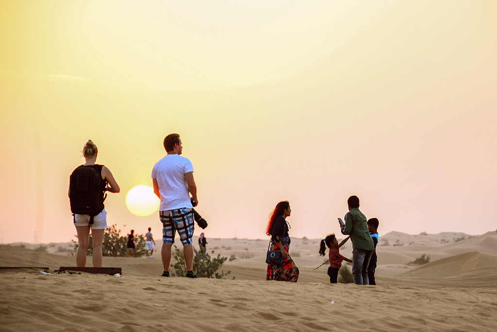 Desert Safari Dubai, people standing in the desert watching the sun go down
