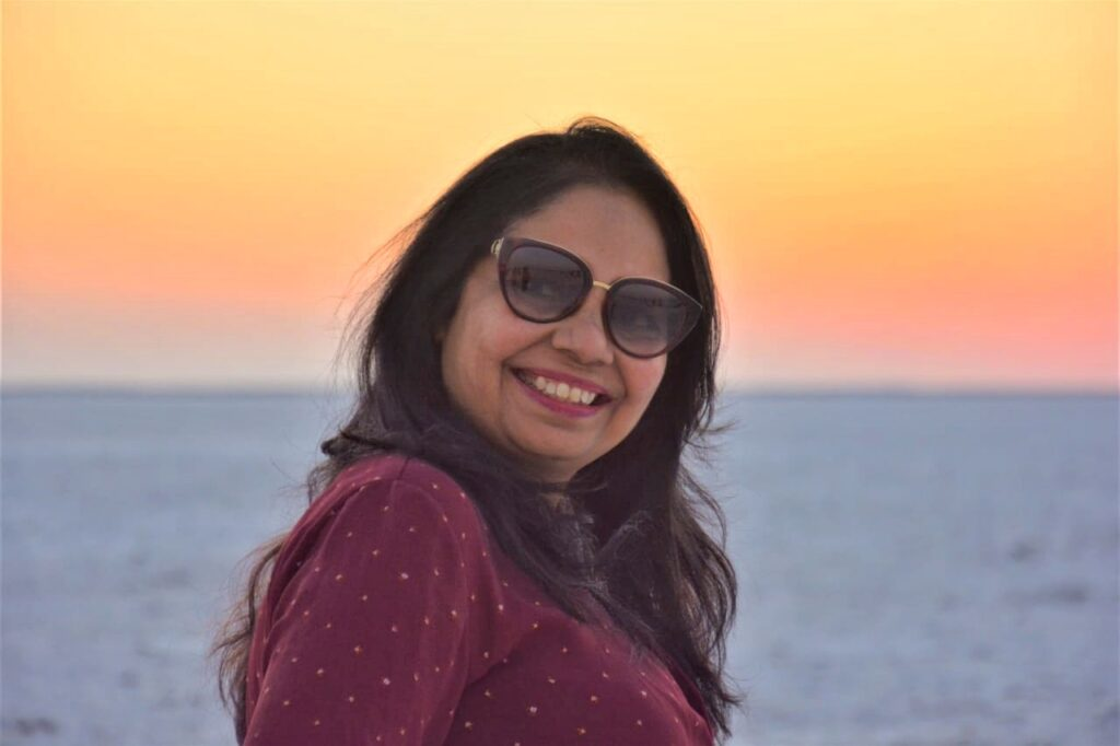 Nilima, behind her a setting or rising sun above the sea. She has sunglasses on