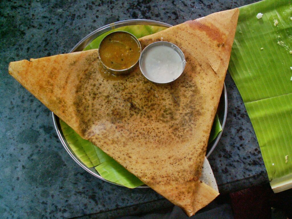 Dosa, dosa on a plate, folded, with 2 small cups with sauce on top of it