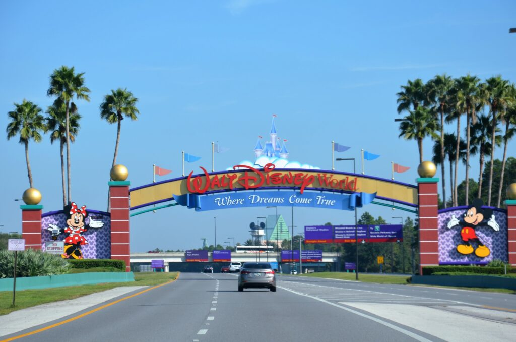 Entrance to Walt Disney World, a car driving on the road going under the sign.