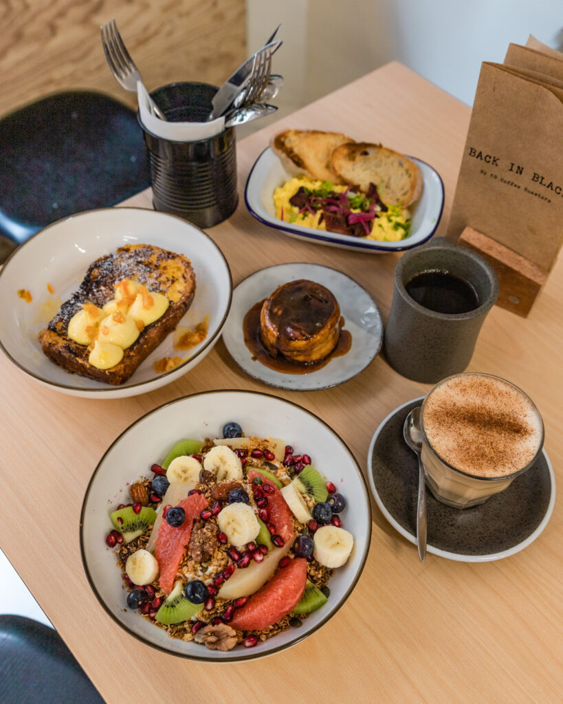 Back in Black by Limitless Secrets, coffee and bowls and plates with food presented on a table