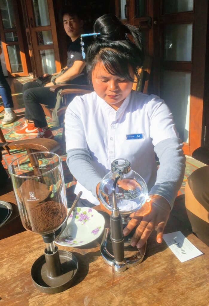 Cafe de Laos by World Travel Connector, a woman making coffee with a special press