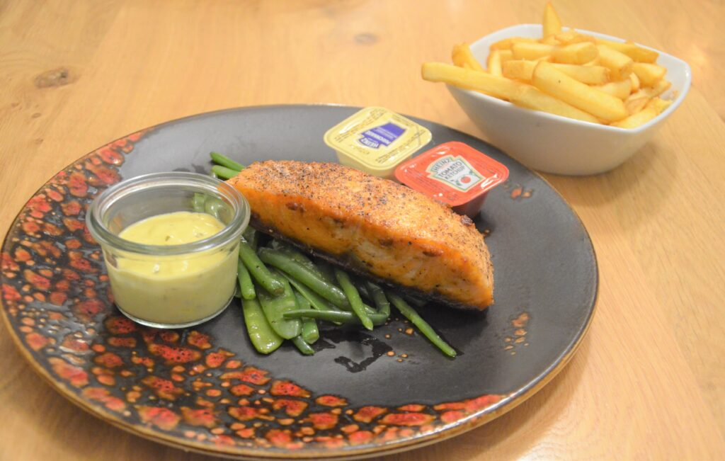 Salmon with bearnaise sauce and fries. On green beans