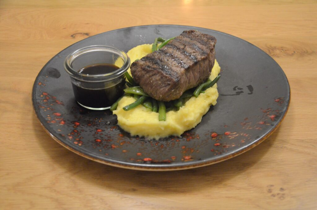 Entrecote on green beans and mashed potatoes with a black sauce on the side