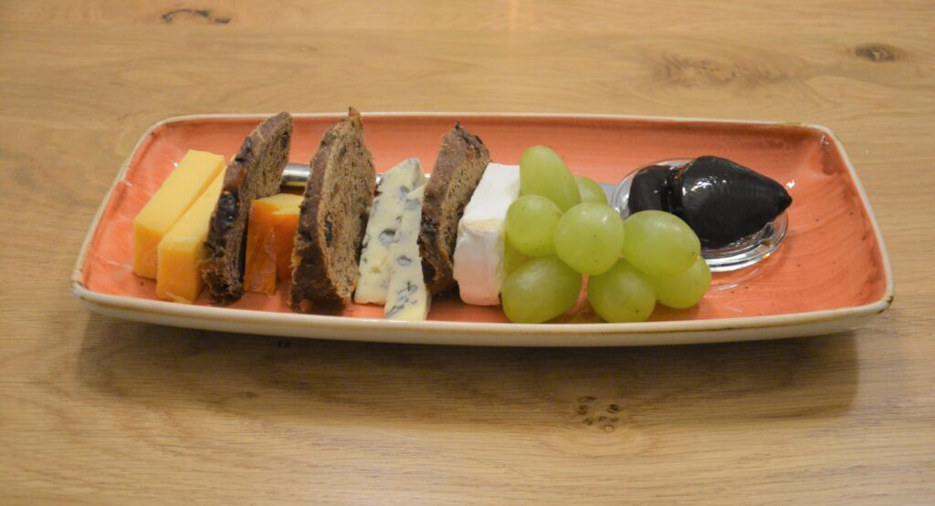 Cheese plate with several different cheeses, grapes, treacle and rye bread