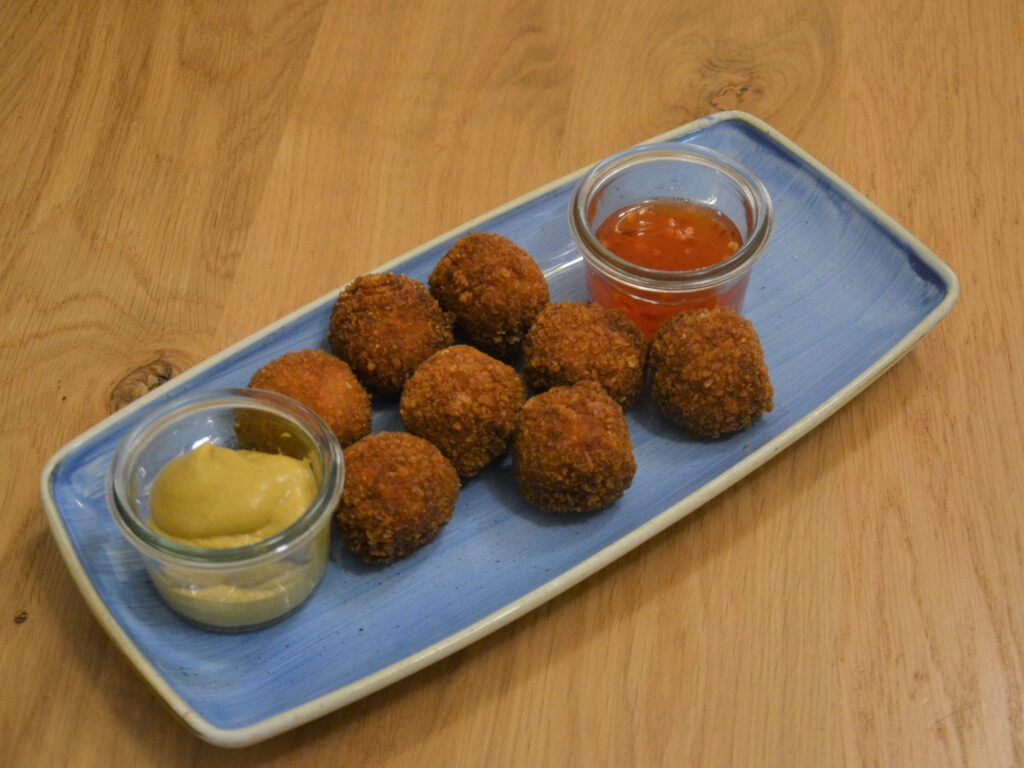 Bitterballen on a blue plate with mustard and sweet chili sauce