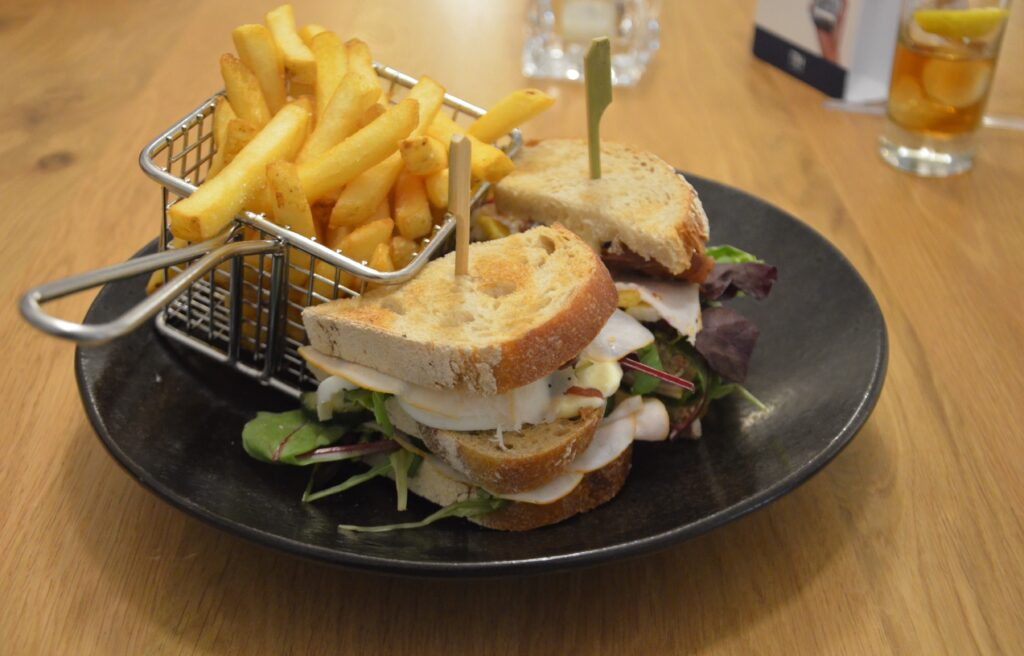 Club sandwich on a black plate with fries on the side