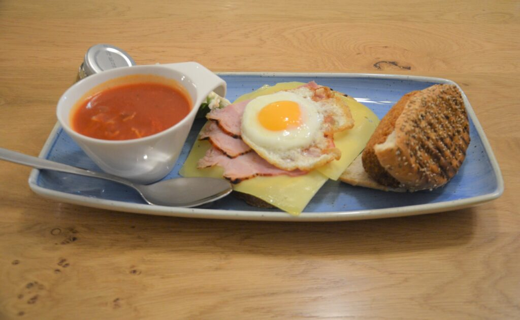 'Twaalf'-uurtje, with tomato soup on the left, an egg sunny side up with ham and cheese and bread under it in the middle and a bun with kroket on the right