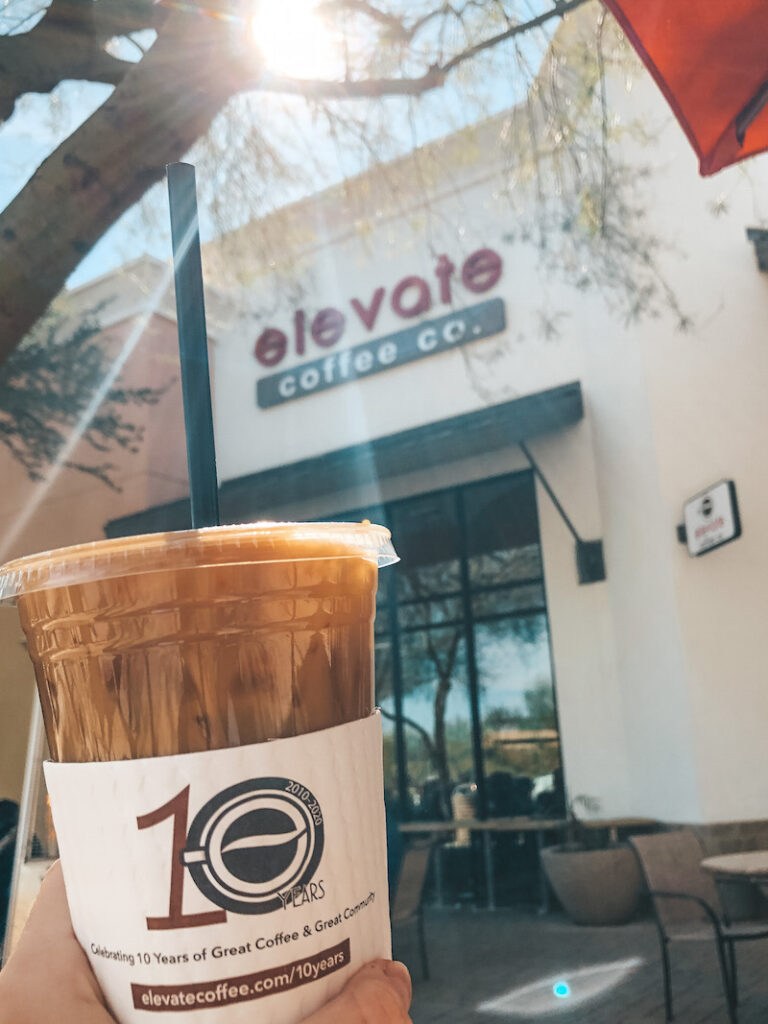 Elevate Cafe by Travel by Brit, a cold coffe in a plastic cup hold in front of the store