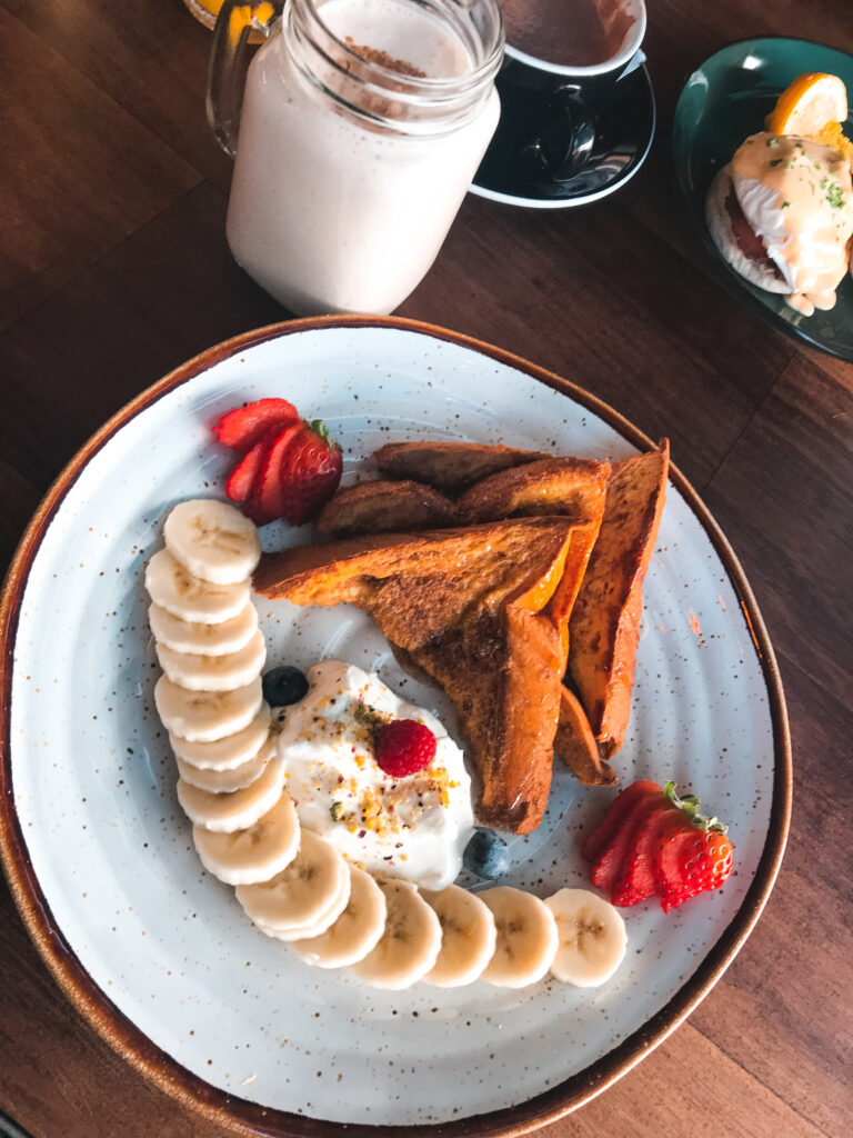 Nicolau Cafe by My Little World of Travelling, breakfast on a plate with toast, strawberries., banana