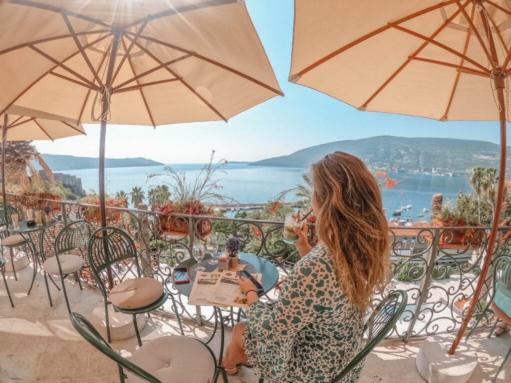 Gradska Kafana by Adventures with Luda, a woman seen from the side, sitting on a terrace overlooking the sea.
