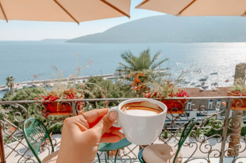 Gradska Kafana by Adventures with Luda, someone is holding a cup of coffee in the foreground. Sitting on a terrace, overlooking the sea.