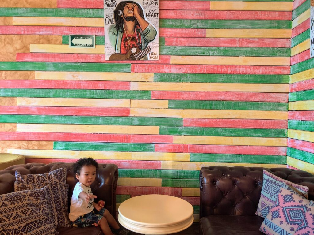 Marley's Coffee by Itz a Family Thing, a small child sitting on a couch, with a table in front and another couch, colored wall and a photo of Bob Marley