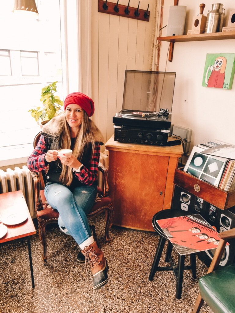 Roasters by Paula Pins the Planet, Paula sits inside the cafe on a chair. An eclectic vibe