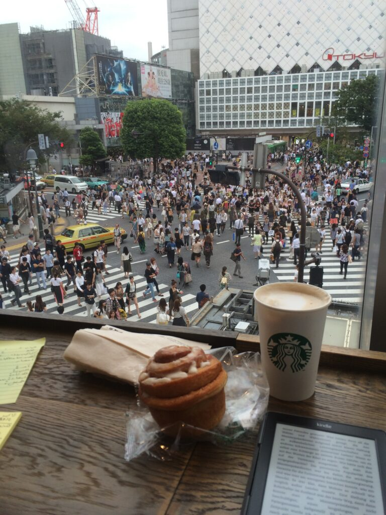 Shibuya by JOURNICATION Travel Blog, from inside the Starbucks you see the Shibuya crossing, with a lot of people crossing the street orderely