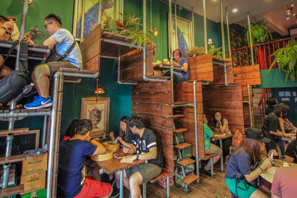 The Lhong Tou Café @ Jürgen Reichenpfader, people sitting in wooden baracks