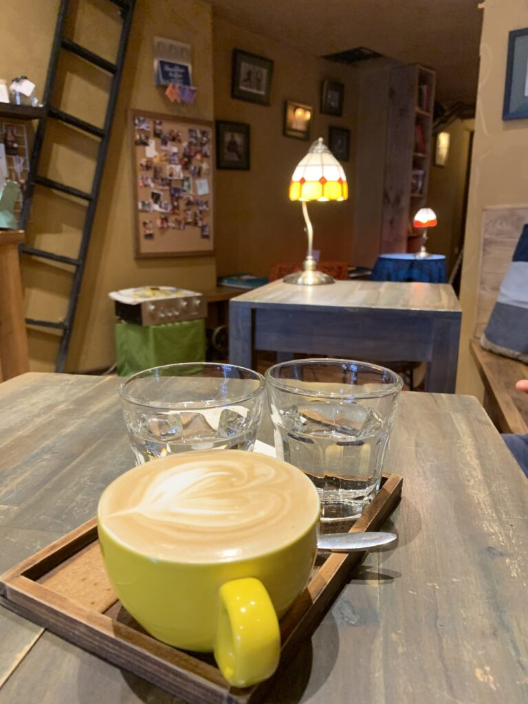 Tranquil Artisan Coffee by Luxury Voyager, a cup of coffee on a table, with the rest of the cafe behind it