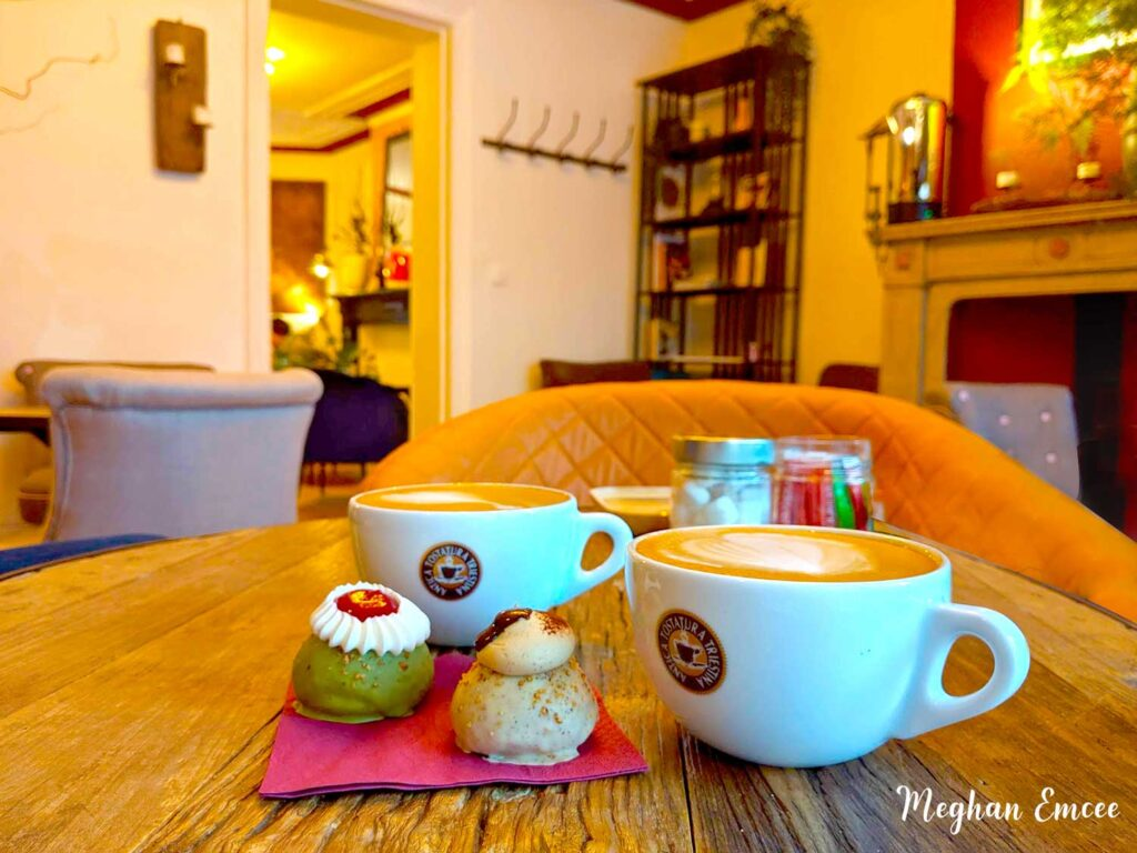 Chouconut by AfterNoon Tea Reads, 2 cups of coffee with choux on a table. In cozy surroundings
