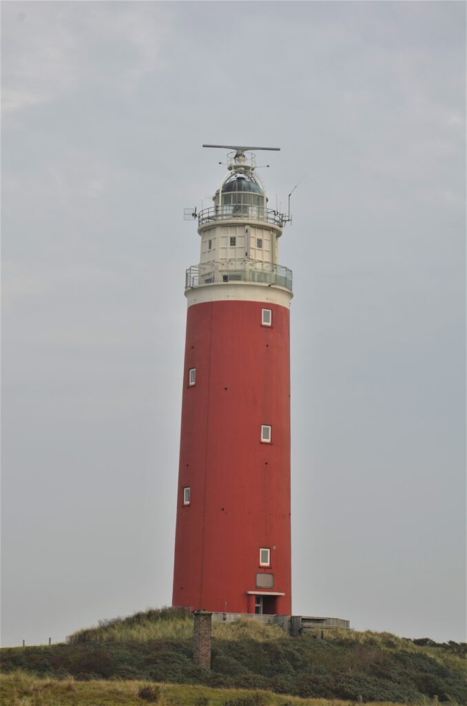 Lighthouse, a red colored lightshouse against a clouded sky